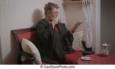 Old woman reading her book. Drink tea