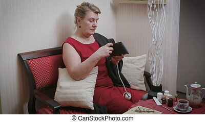 older woman is measuring blood pressure. In home
