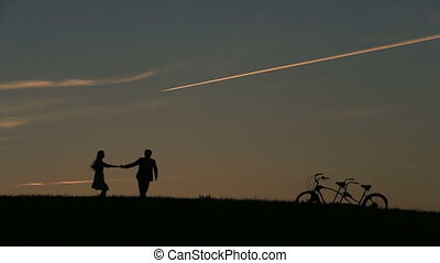 Silhouette of Beautiful Couple With Tandem Bicycles Playing...