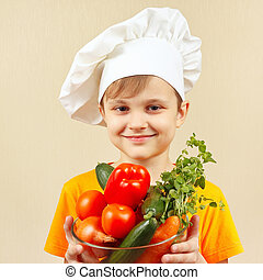 Little smiling boy in chefs hat with fresh vegetables