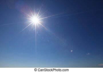 Sun with lens flare in clear blue sky
