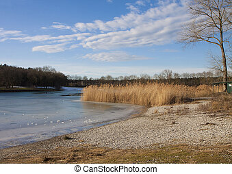 Winter scene in Bavaria - lake with ice melting on surface -...