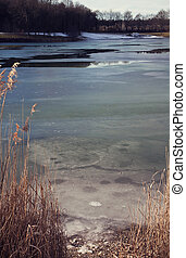Winter scene in Bavaria - lake edge with iced surface on a...