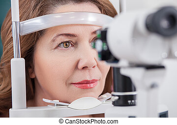 Cheerful lady having eye examination in oculist office -...