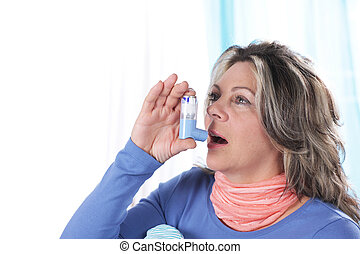 Matured woman inhales asthma spray in bed