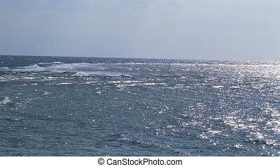 Calm ocean with blue sky .