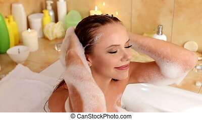 Woman taking bath and wash hair by shampoo in her bathroom -...