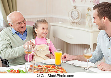 Pretty friendly family has a dinner with joy - Cheerful old...