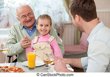 Cheerful mature grandfather is dining with his children -...