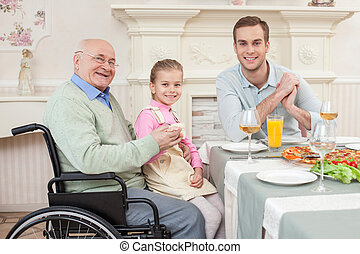 Cheerful old disabled grandfather with his family - We are...