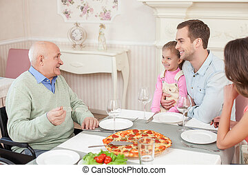 Pretty friendly family is dining in cafe - Cute senior man...