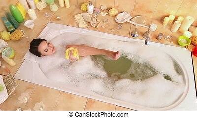 Woman taking foam bath and chiropody by wisp of bast in her...