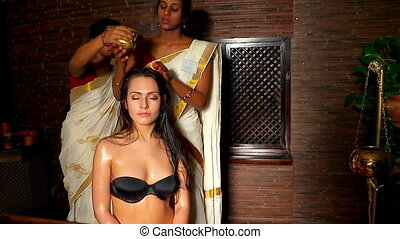 Young woman having head ayurveda treatment. Indian female masseuse in  ayurvedic spa salon.