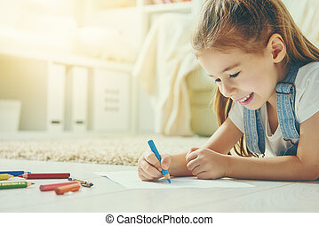 Happy child plays. Little child girl draws with colored...