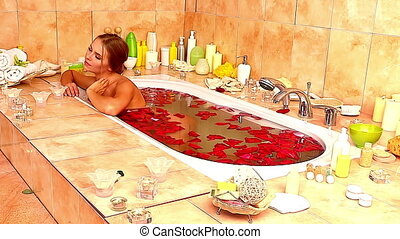 Girl taking bath with rose petals. Time lapse.