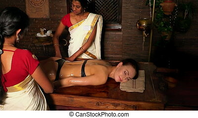 Woman girl lying on her stomach and having spa treatment. Two real Indian masseuses massage hands.