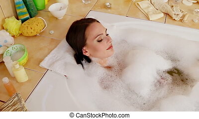 Woman taking bath and blowing on foam in her bathroom -...