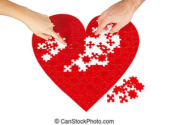 Red heart puzzles - Young couple assembling a red puzzle...