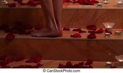Girl taking bath with rose petals in spa Dolly crane system...