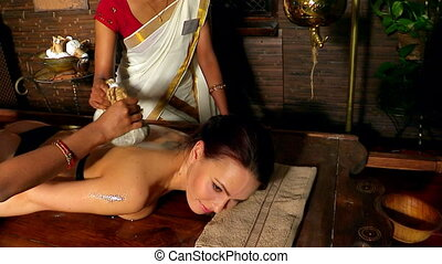 Woman having ayurvedic back massage with pouch of rice One...