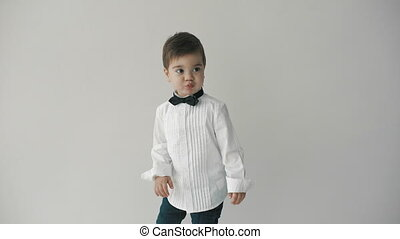 little cute boy in bowtie smiling, making funny faces,...