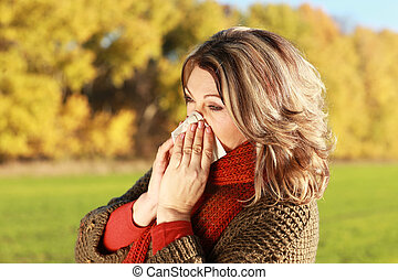 Middle age woman with handkerchief and cold outdoor blowing...