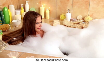 Woman taking a bath and blowing on foam in her bathroom. -...