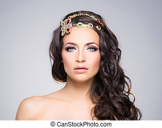 Attractive, curly brunette with flower alike golden headband...