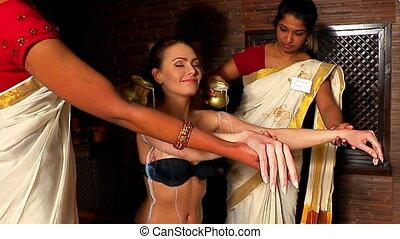Woman having Ayurvedic spa treatment Two real Indian...