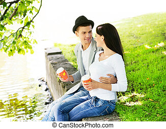 Young couple sitting together on the riverside and drinking...