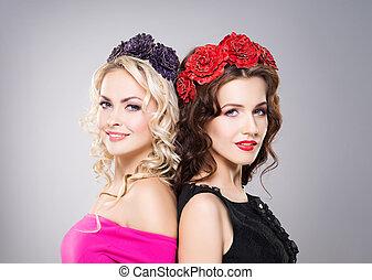 Portrait of two gorgeous, smiling women wearing flower alike...