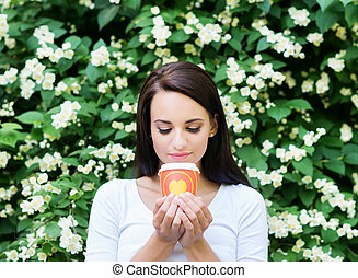 Attractive girl enjoying a cup of coffee in the nature