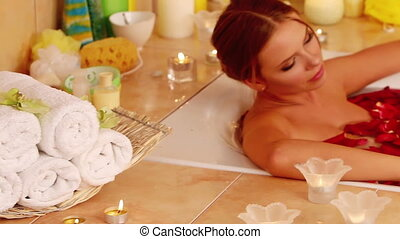 Young woman is relaxing with rose petals bath in spa salon -...