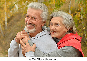 Senior couple in autumn park - Portrait of a happy senior...