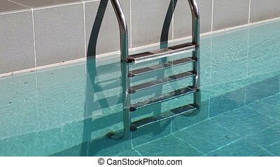 Water splashing in the outdoor swimming  pool with metal ladder