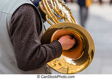 Man with a trumpet - male street musician playing on the...