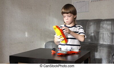 boy playing with lots of colorful plastic blocks indoor -...