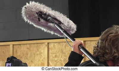 Filming interview - Close up of professional boom operator...