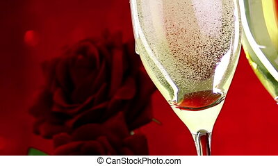 pouring champagne flutes with bubbles near red roses on red...