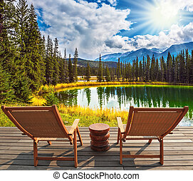 Two wooden deckchairs on the shore of lake