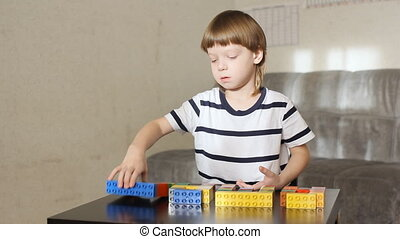 boy playing with lots of colorful plastic blocks indoor