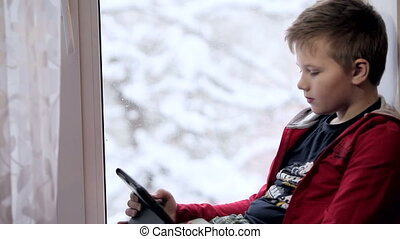 Boy, playing on tablet - Boy, sitting on the window, playing...