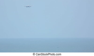 Airbus 330 approaching over ocean before landing in...