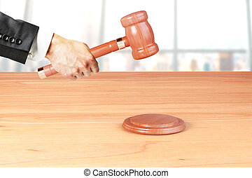 Man hand with gavel on wooden table