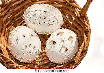 three perforated Easter eggs in wicker basket