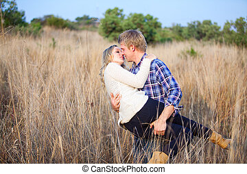 Young man playfully picking up his girlfriend for a kiss