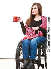 Woman invalid girl on wheelchair holds tea mug - Real...