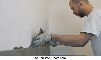 Home improvement, renovation - construction worker tiler is tiling, ceramic tile wall adhesive, trowel with mortar