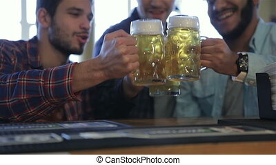 Men with beer rejoice the victory of team - Three men with...