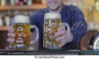 Bartender holding beer glasses and smiling - Adult man...